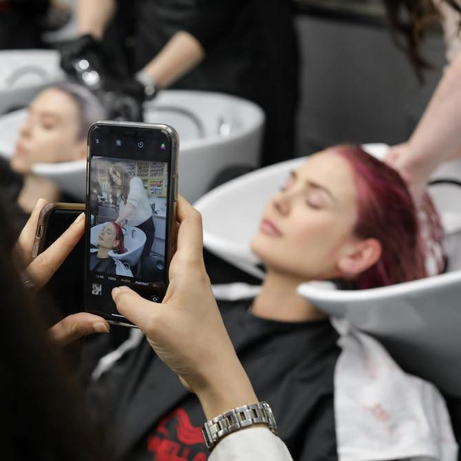 Hairdresser using a phone to take a photo of a woman having her hair washed.