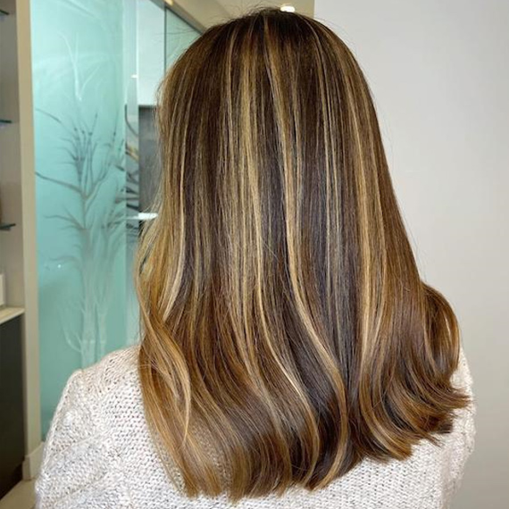 Back of woman's head with brown hair and blonde chunky highlights, created using Wella Professionals.