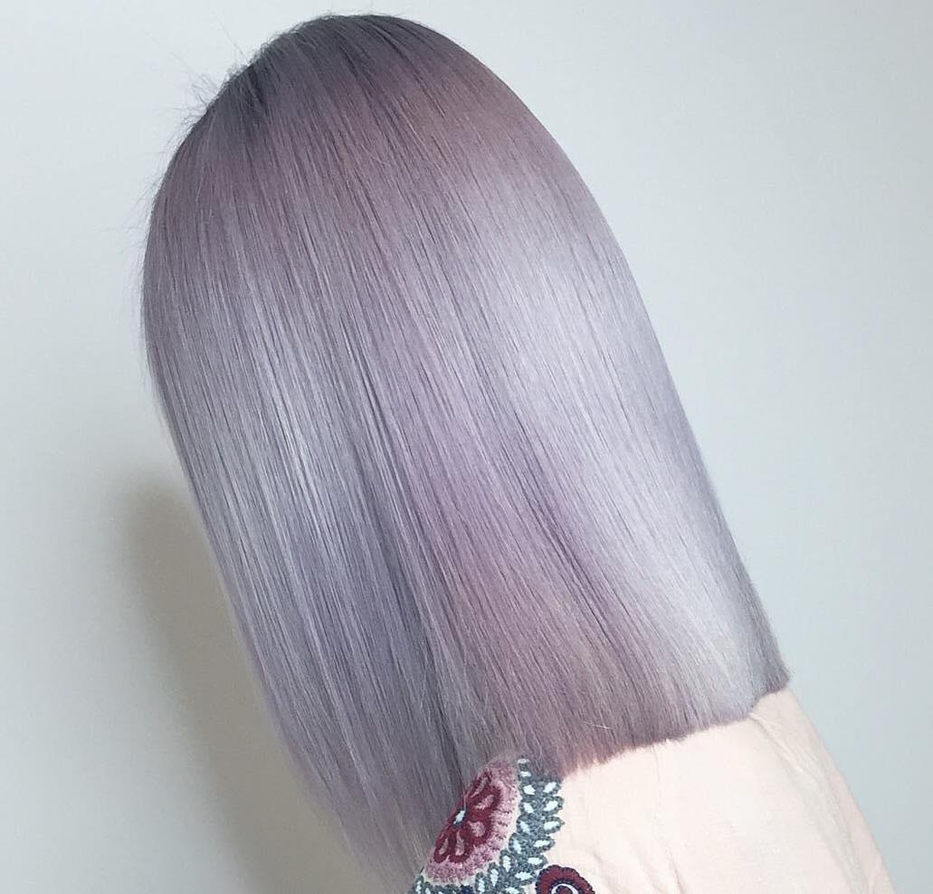 Back of womans head with straight icy violet hair color