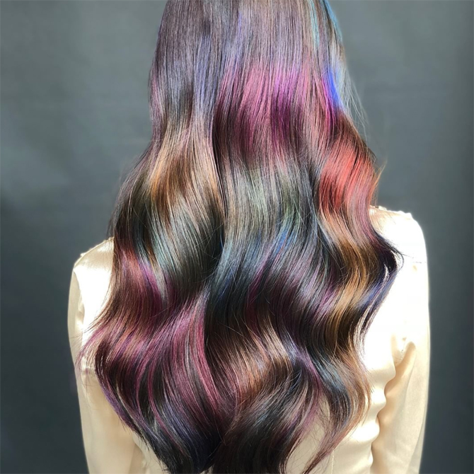 Back of woman's head with multicolored metalic color melts on brown hair