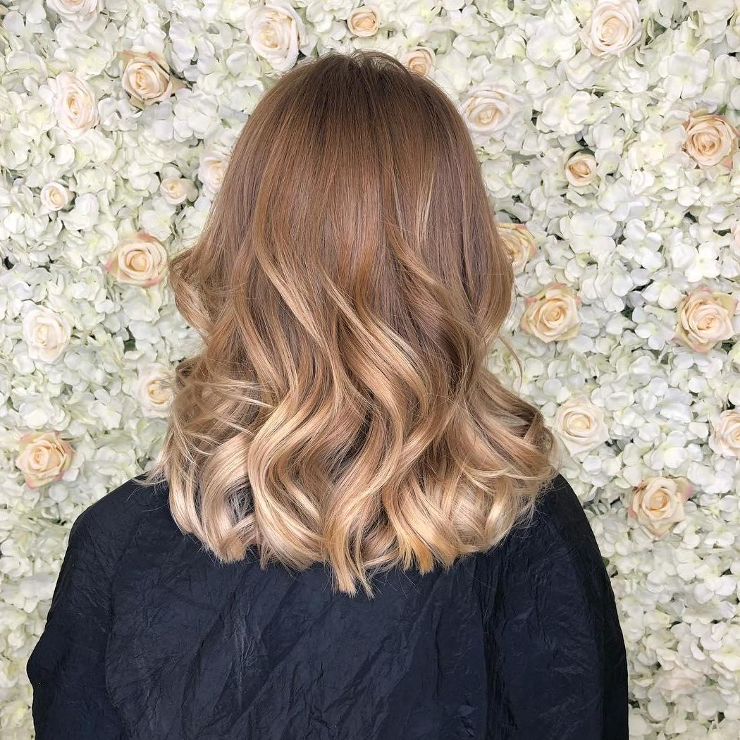 Woman with mid length, dirty blonde, balayage hair styled with loose waves