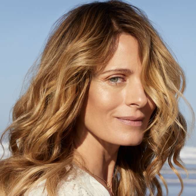 Woman with long brown hair and blonde Illuminage, created using Wella Professionals.