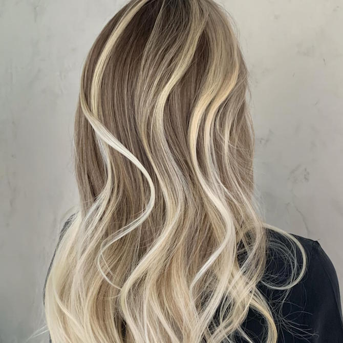 Back of woman's head with chunky, platinum blonde highlights through long, wavy hair.