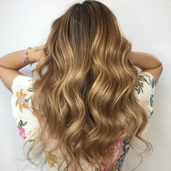 Back of woman's head with long, wavy, golden toffee hair, created using Wella Professionals.