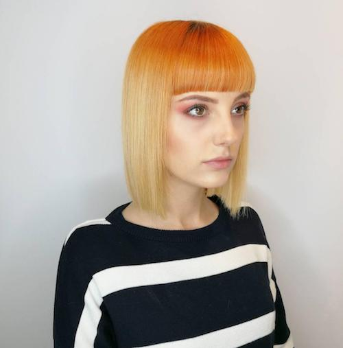 Woman with short blunt cut bob and fringe with orange blonde ombre color