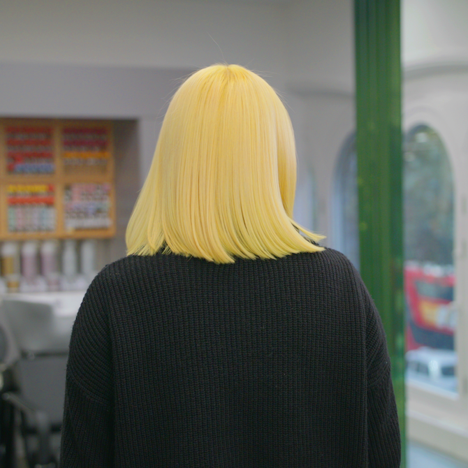 Woman with bright neon yellow straight blunt cut bob