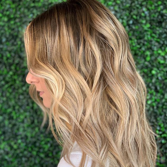 Side profile of woman with beach blonde, wavy hair, created using Wella Professionals.