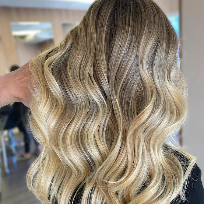 Back of woman's head with long, wavy, tousled, beach blonde hair, created using Wella Professionals.