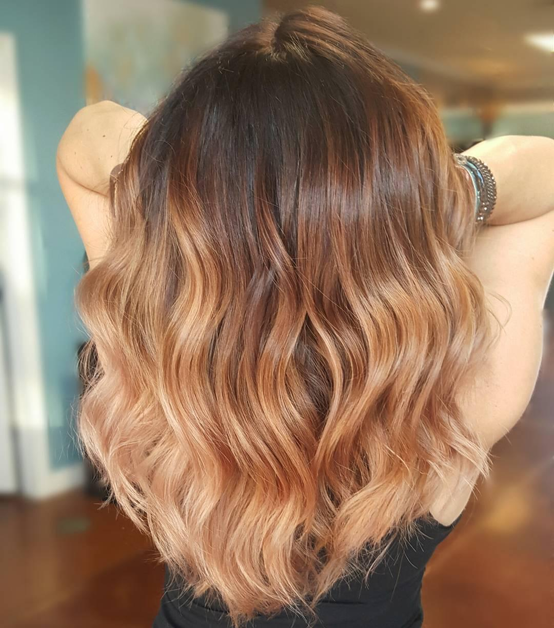 Back of woman's head with dark roots and caramel blonde hair styled with loose waves