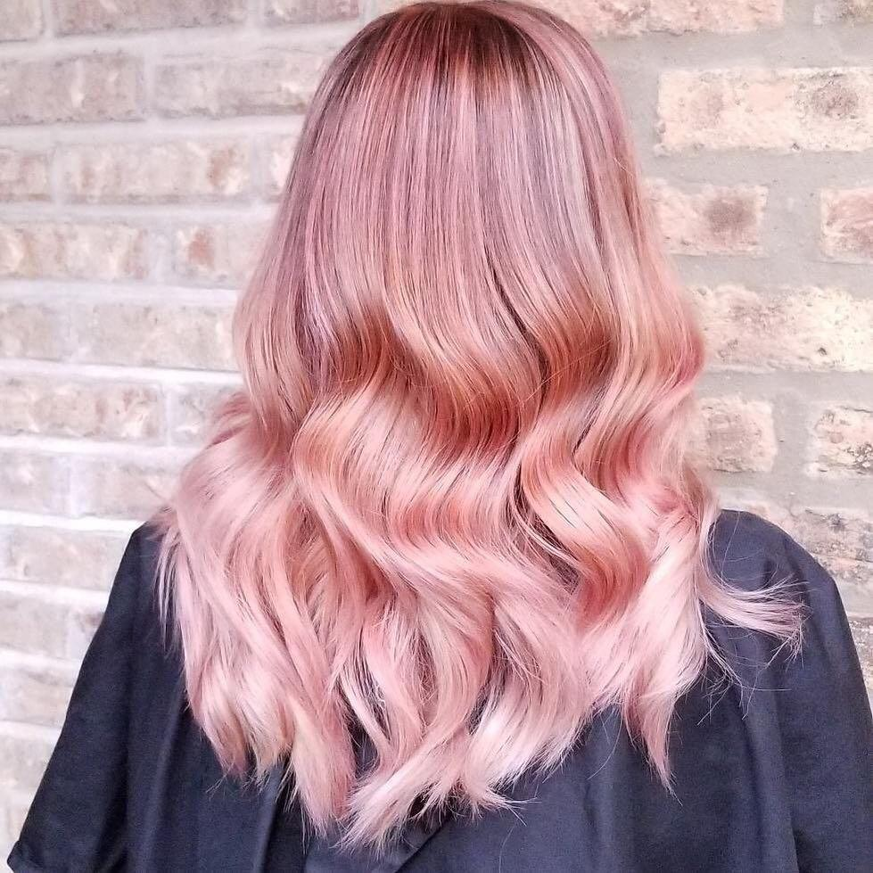 Woman with long metallic rose gold hair styled with loose waves
