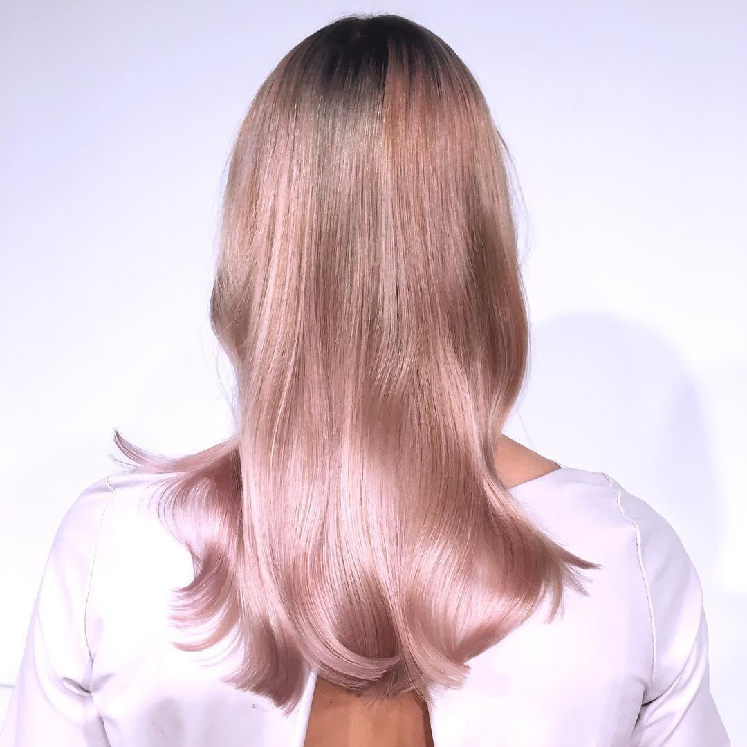 Back of womans head with long straight pastel pink hair and dark roots