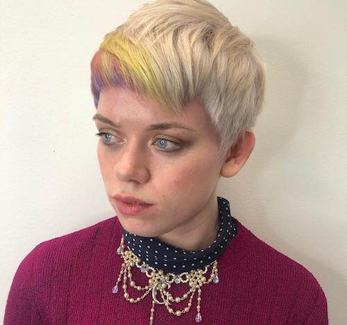 Woman with short ice blonde hair with rainbow fringe