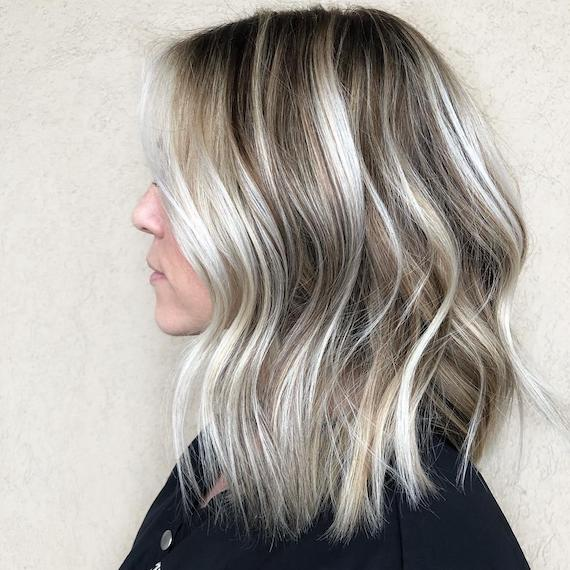 Side profile photo of a woman with blonde balayage, created using Wella Professionals