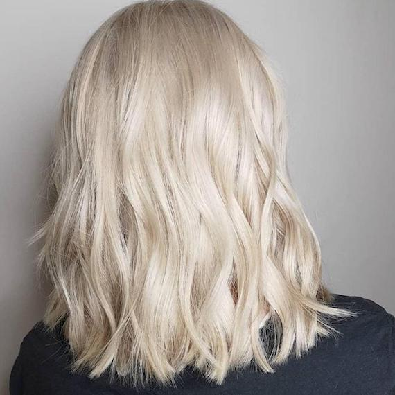 Photo of the back of a woman's head with wavy cream blonde hair, created using Wella Professionals