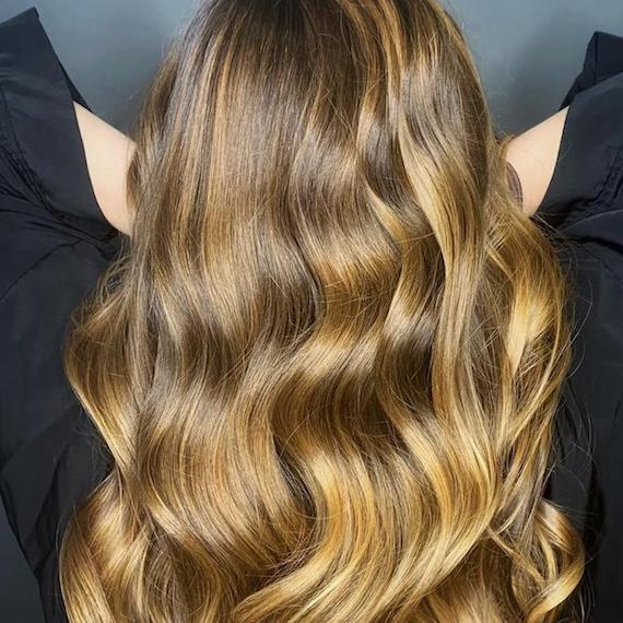 Photo of the back of a woman's head with wavy caramel blonde hair, created using Wella Professionals