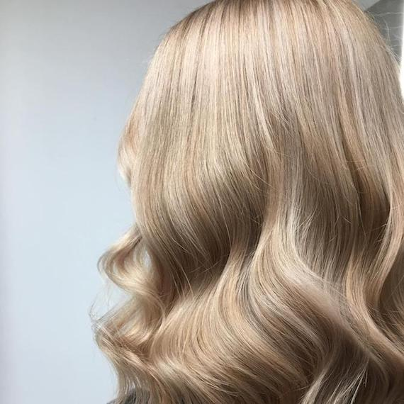Photo of the back of a woman's head with wavy beige blonde hair, created using Wella Professionals