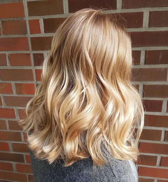 Photo of the back of a woman's head with wavy golden blonde hair, created using Wella Professionals