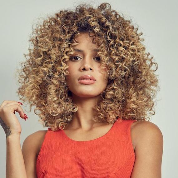 Woman facing the camera with curly, caramel blonde hair, created using Wella Professionals