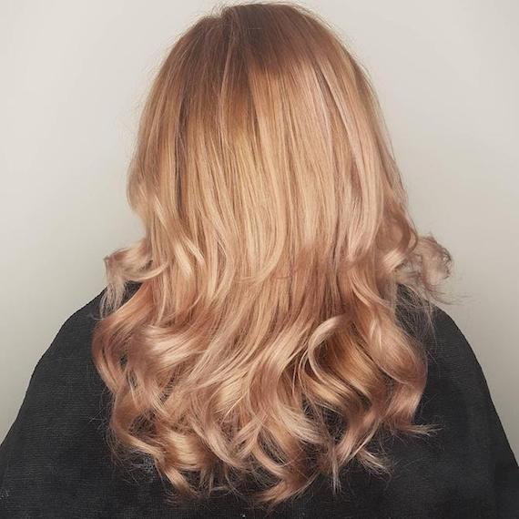 Photo of the back of a woman's head with wavy champagne blonde hair, created using Wella Professionals