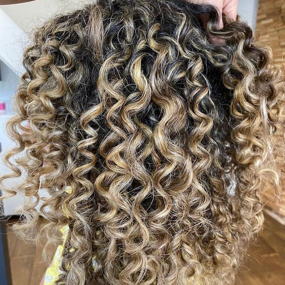 Side profile of woman with beachy blonde curly hair, created using Wella Professionals.