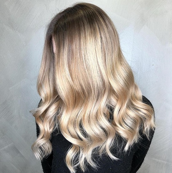 Woman with cream soda blonde hair, created using Wella Professionals.