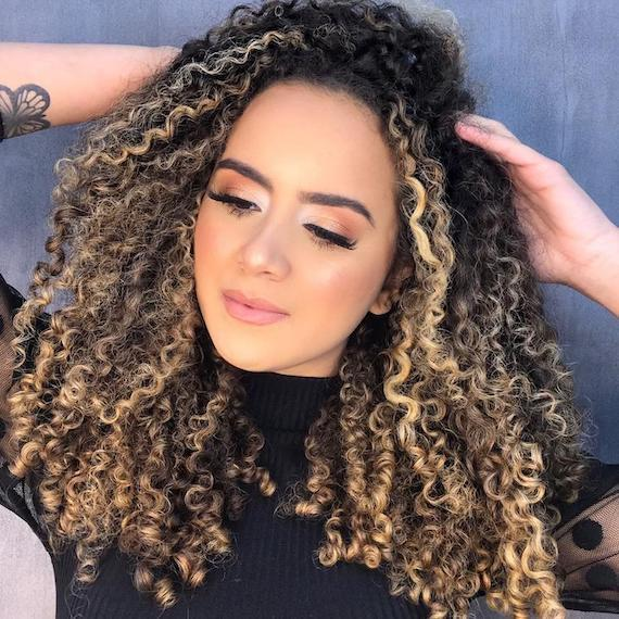 Woman with twilighting highlighting through curly hair, created using Wella Professionals.