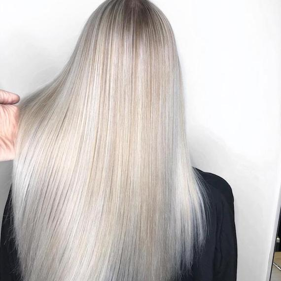 Photo of the back of a woman's head with long, straight, silver blonde hair, created using Wella Professionals