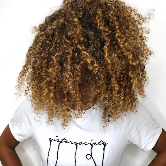 Woman with bronde highlights through curly hair, created using Wella Professionals
