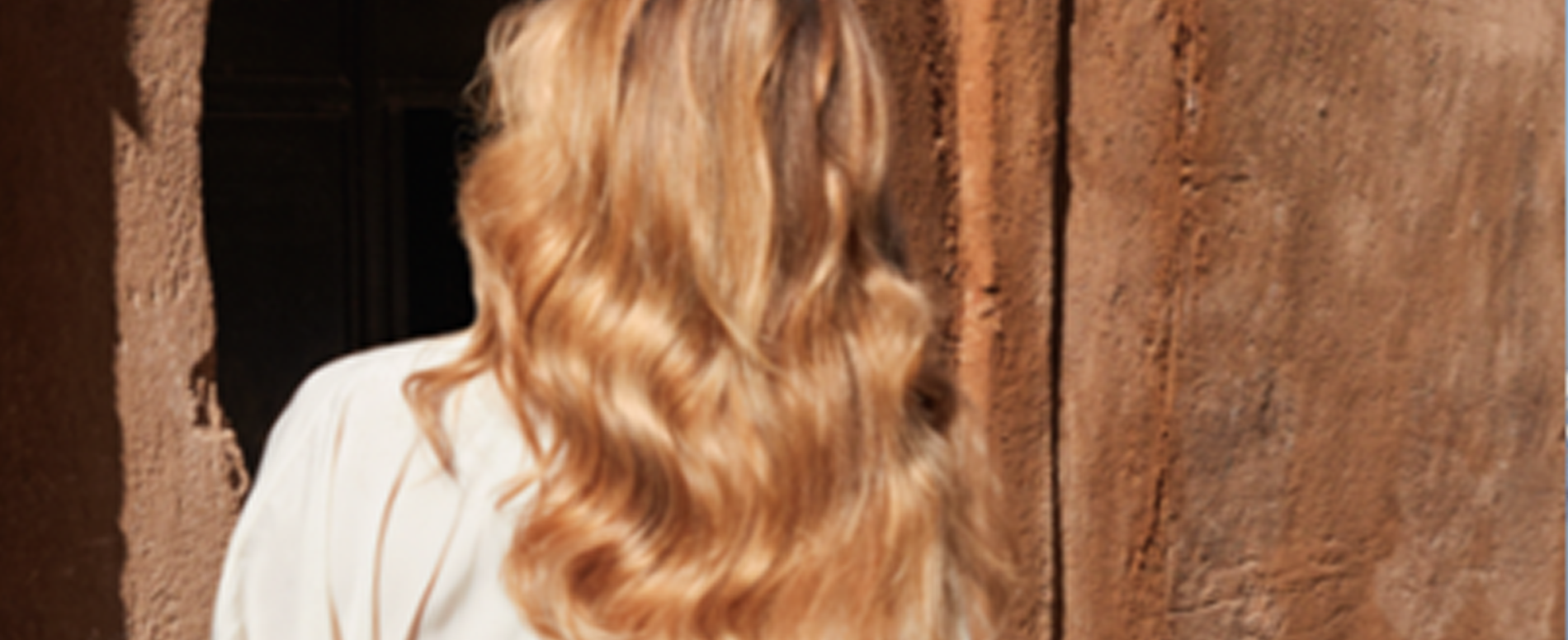 Back of a woman's head with sun-kissed hair, created using Wella Professionals' Illuminage technique.