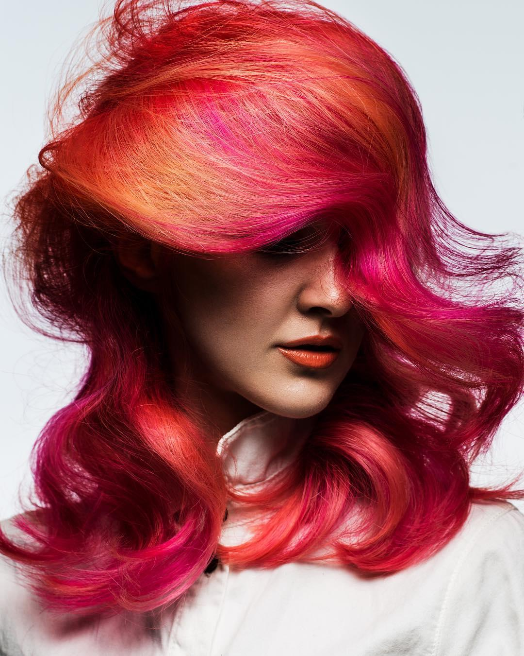 Woman with bright orange red pink hair, styled with loose waves