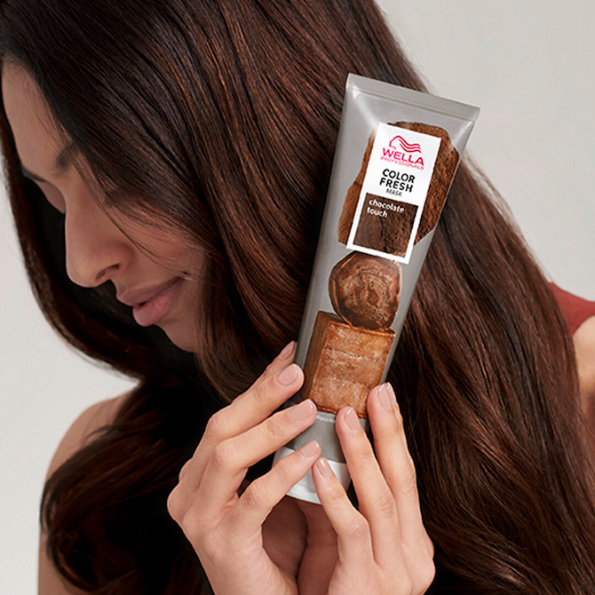 Brunette model looking to the side as she holds up a tube of Wella's Color Fresh Mask in Chocolate Touch.