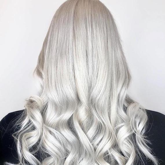 Back of woman's head with long silver gray hair, created using Wella Professionals.