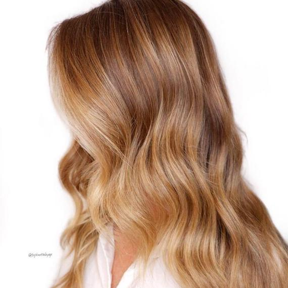 Side profile of woman with golden blonde hair, created using Wella Professionals.