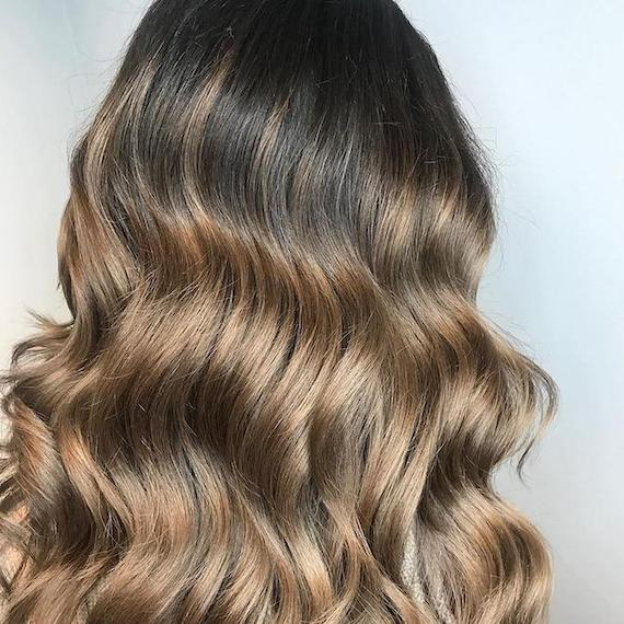 Side profile of woman with long, wavy, ash bronde hair, created using Wella Professionals.