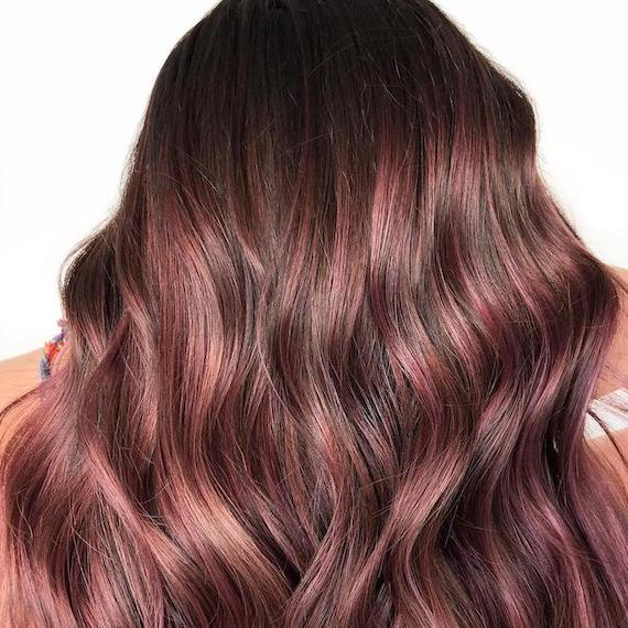 Back of woman's head with raspberry chocolate, wavy hair, created using Wella Professionals.