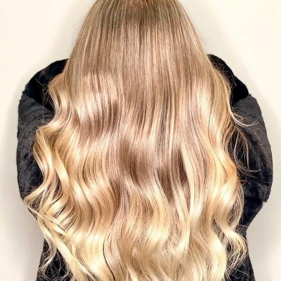 Back of woman's head with long, sunlight blonde hair in loose curls, created using Wella Professionals.