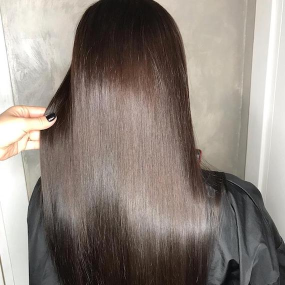 Back of woman's head with long, silky-straight, dark brunette hair, created using Wella Professionals.