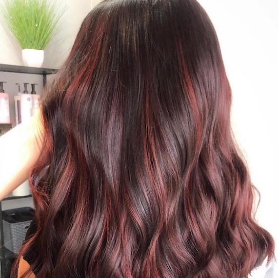 Back of woman's head with long, wavy, cherry chocolate hair, created using Wella Professionals.