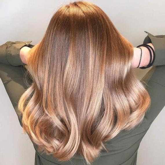 Back of woman's head with long, glossy, bronde balayage hair, created using Wella Professionals.