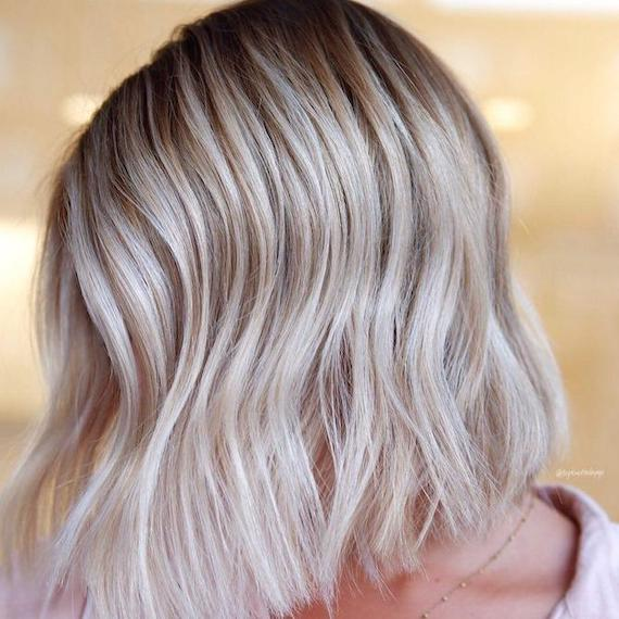 Side profile of woman with rooted platinum hair, created using Wella Professionals.