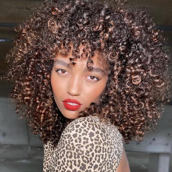 Woman facing camera with curly, frosted chestnut hair, created using Wella Professionals.