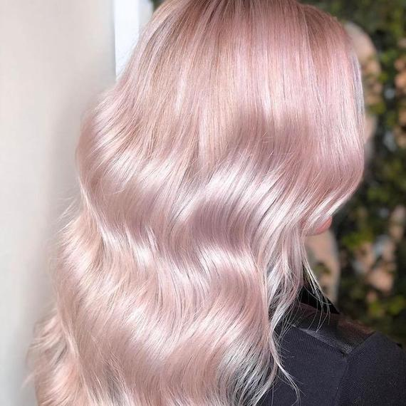 Back of woman's head with wavy, pastel pink hair, created using Wella Professionals.
