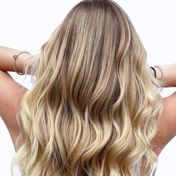 Back of woman's head with wavy, beach blonde hair, created using Wella Professionals.