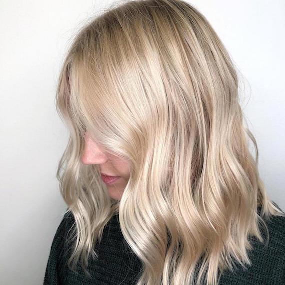 Seitenprofil eines Models mit gelocktem, blondem, mittellangem Haar, kreiert mit Wella Professionals.