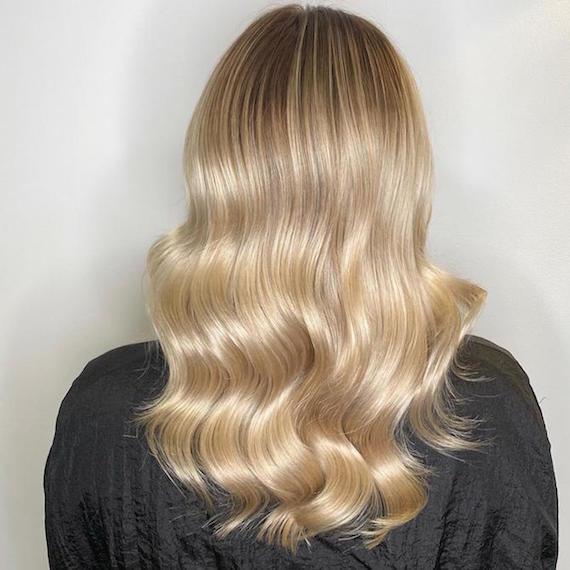 Hinterkopf einer Frau mit langem, goldblondem Haar, kreiert mit Wella Professionals.
