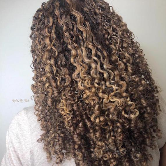 Seitenprofil eines Models mit langem, gelocktem, blondem Haar, kreiert mit Wella Professionals.