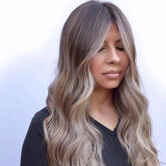 Woman with long, ash brown, balayage hair, created using Wella Professionals.