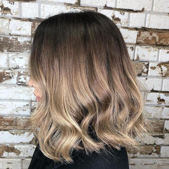 Side profile image of a woman with short hair and ash brown ombre hair color, created using Wella Professionals.