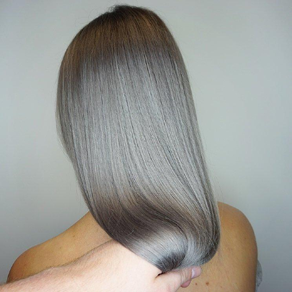 back of woman's head with sleek, straight hair dyed silver ash gray