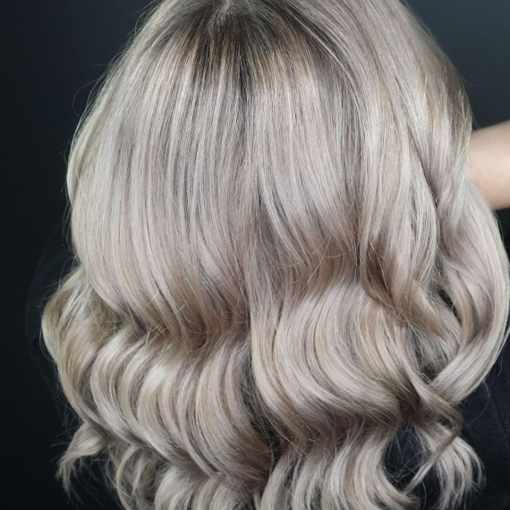 back of woman's head with wavy, ash gray blonde hair